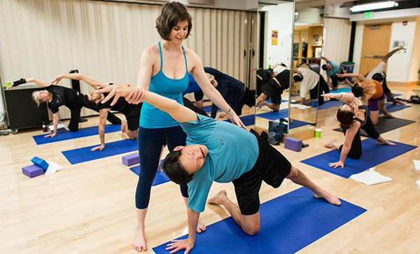 Image of Erin offering a hands-on assist for a student in downward facing dog